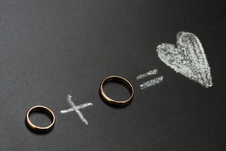 Foto de Wedding rings and plus and heart drawing with calk on calkboard. Husband and wife or groom and bride, married couple concept. - Imagen libre de derechos