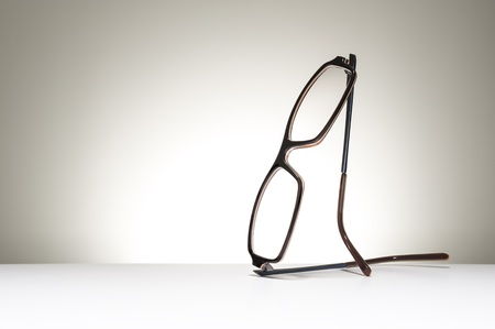 Pair of modern fashionable spectacles balanced in an upright position on a white studio background with copyspace conceptual of vision, correction, optometry and healthcare