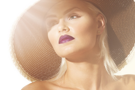 Close up head shot of a gorgeous sophisticated exotic young blond woman wearing a wide brimmed hat facing into sun flare