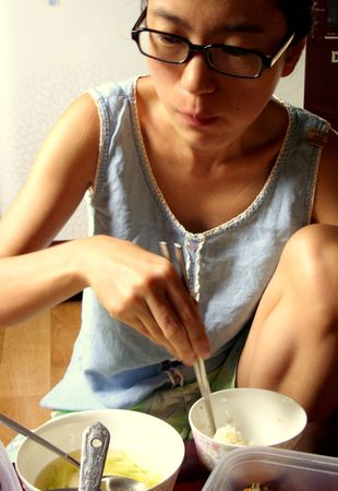 asian girl with glasses eating with chopsticks