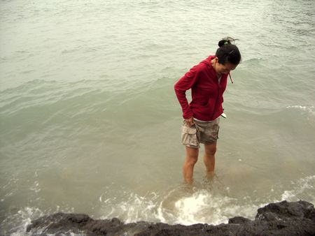 a girl with red jacket in the sea