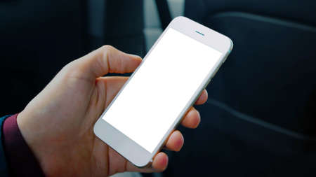 Photo pour Man hand holding a cell phone with a blank white screen smartphone, interior car background, black copy space. - image libre de droit