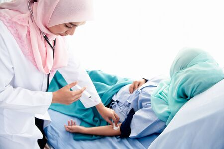 Photo pour A beautiful young Muslim woman doctor wearing headphones, hand-held syringes, and a cotton ball is about to be injected into the arm of a sick patient lying on a bed in a hospital examination room. - image libre de droit