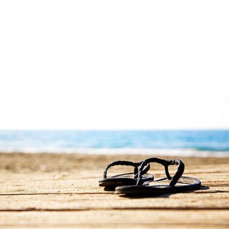 Black summer sandals on the sandy dock