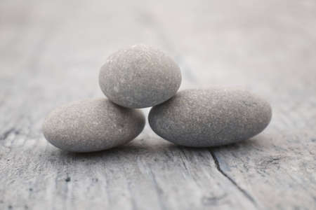 three round and soft stones on a old piece of wood