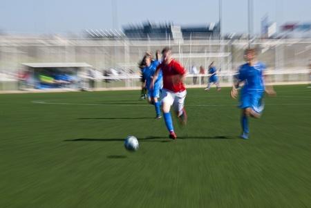 Un match de football, des personnes en courant aprÚs le ballon, en tentant consegirlo avant que les demas. L