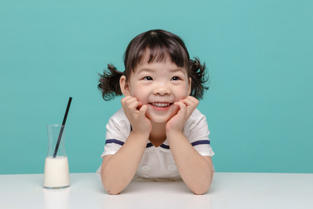 Foto de Little pretty Asian girl laughing portrait with milk, healthy and happy lifestyle. - Imagen libre de derechos