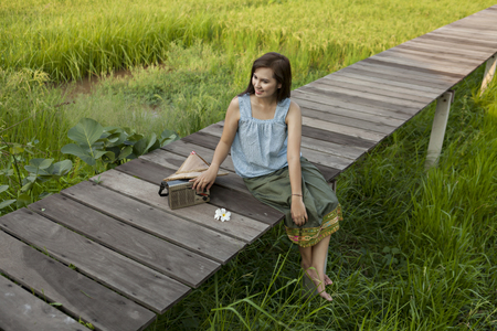 A peasant girl listening to the radio on a wooden bridge in a field,countryside Thailand