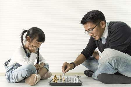 Foto de Happy asian family playing chess together. - Imagen libre de derechos