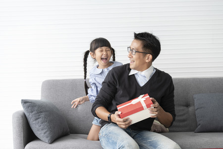 Photo pour Asian father give present for daughter. concept surprise gift box for birthday. - image libre de droit
