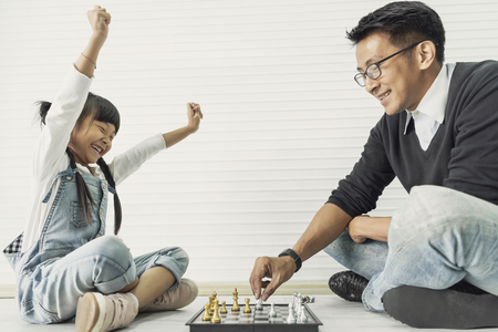 Photo pour Happy asian family playing chess together at home. - image libre de droit