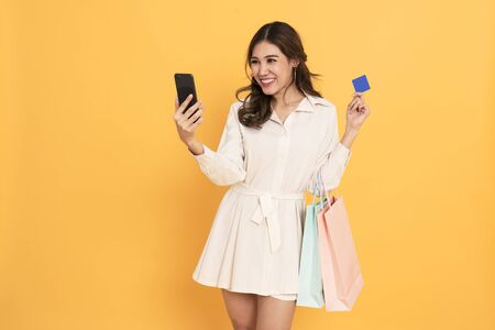 Photo for Asian women shopper using mobile phone and credit card for making payment. black friday and shopping online concept isolated on yellow background. - Royalty Free Image
