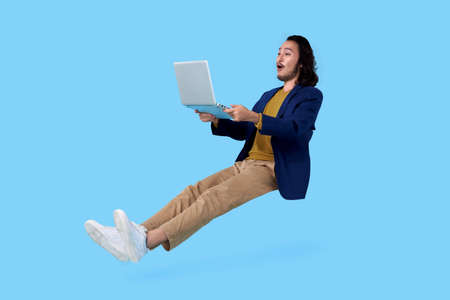 Photo pour Young asian businessman hand holding computer laptop floating in mid-air isolated on blue background. - image libre de droit