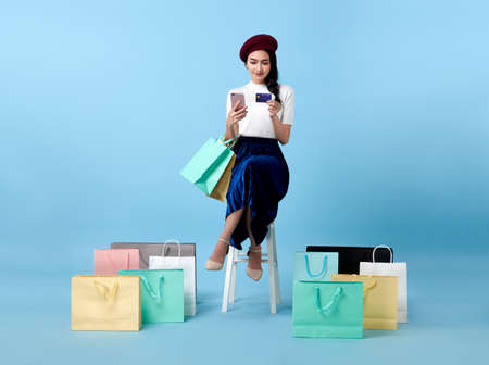 Photo pour Beautiful Asian woman shopper sitting and carrying shopping bags with using credit card and mobile phone in hands on blue background. - image libre de droit