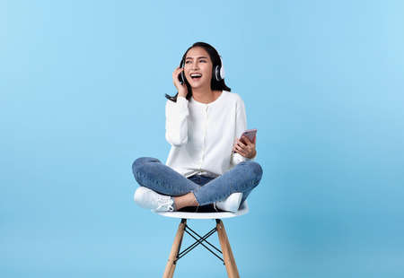 Photo pour Young woman asian happy smiling wearing wireless headphones listening to music from smartphone on white chair isolate on bright blue background. - image libre de droit