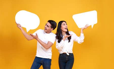 Photo pour Smiling happy Asian couple holding blank speech bubbles on yellow background. - image libre de droit