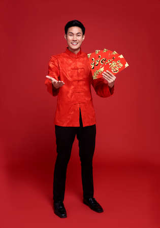 Photo for Happy Chinese new year. Asian man holding angpao or red packet monetary gift isolated on red background. - Royalty Free Image