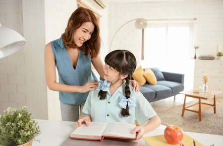 Photo pour Homeschool Asian little young girl student learning sitting on table working with his tutor at home. - image libre de droit