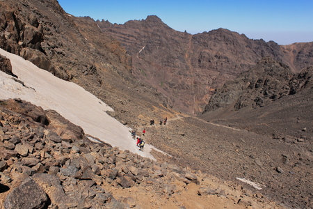 Treking on the highest summit of Morocco. Trail in Altas Mountains. Snow on the slope.