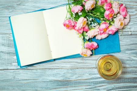 notepad, white wine and flowers, flat lay