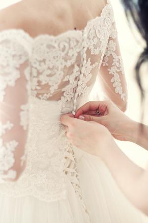 Photo pour the hand of the girlfriend clasps buttons on the bride's corset - image libre de droit