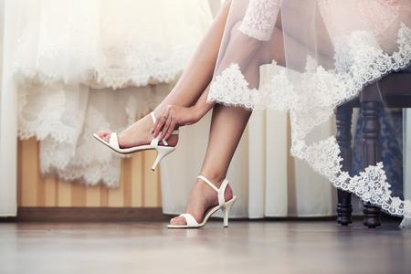 Photo pour the bride puts on white shoes on feet - image libre de droit