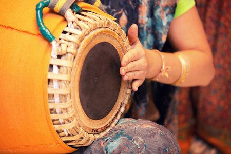 woman playing on traditional Indian tabla drums close up