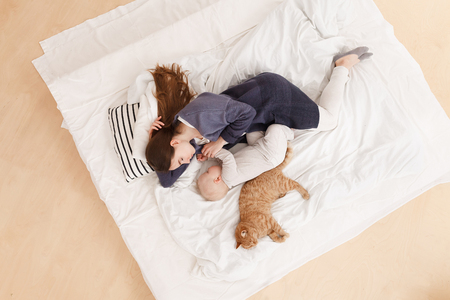 Photo for young caucasian mother sleeps together with baby boy in the afternoon in a bed together with a red cat. Focus on woman, top view. Healthy day sleep. - Royalty Free Image