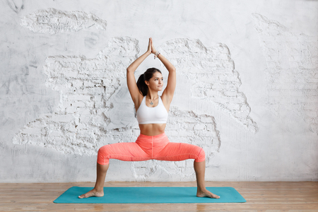 Portrait of young attractive yogi woman practicing yoga concept, standing in Sumo Squat exercise, Goddess pose, working out, wearing sportswear bra and pants, full length, white loft studio, white brick wall background