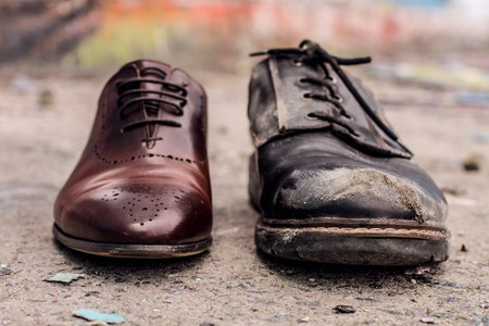 Photo pour Conceptual shooting of shoes. Old shabby shoes in comparison with new and expensive ones. - image libre de droit