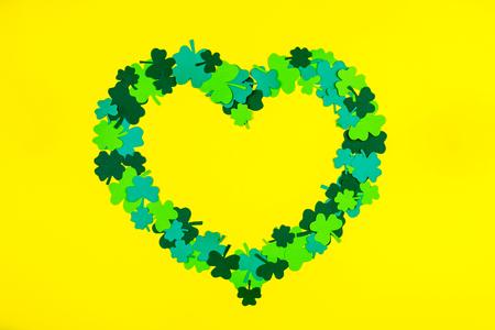 Saint Patrick's Day. Heart shape of green three petal clovers lying on yellow background