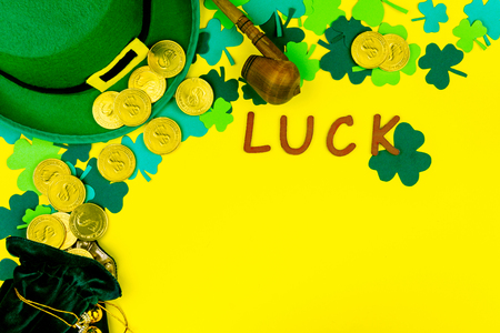 Saint Patrick's Day. Wooden letters luck, little bag with gold coins, green three petal clover, green hat of leprechaun on yellow background