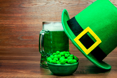 Saint Patrick's Day. Green glass pint of beer, green snacks cookies sweets and green hat of leprechaun on wooden background