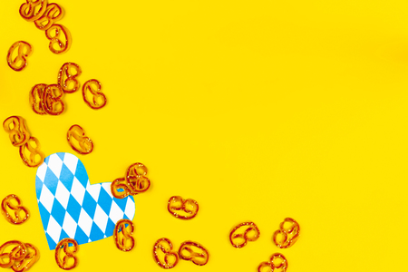 October fest concept. Sweet tasty wheat breads pretzels as snack appetizer to beer with blue decorative heart love on yellow background.  Ads event of october beer festival in autumn october month