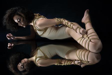 Submission slave woman bound in erotic fashion style rope shibari kinbaku Japanese bondage knot lie on floor with symmetry reflection Bdsm mistress dominant fetish punishment sadism masochism concept.