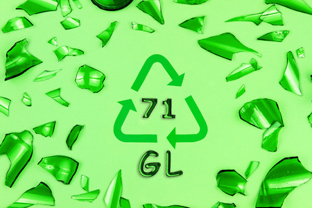 Glass garbage on green background. Recycling reuse code symbol sign with inscription 71 GL in center. Pieces of broken green bottle glass.Trash sorting at home. Save planet, environment care concept