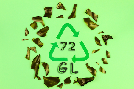 Glass garbage on green background. Recycling reuse code symbol sign with inscription 72 GL in center, surrounded with circle of pieces of broken brown bottle glass.Trash sorting at home. Save planet