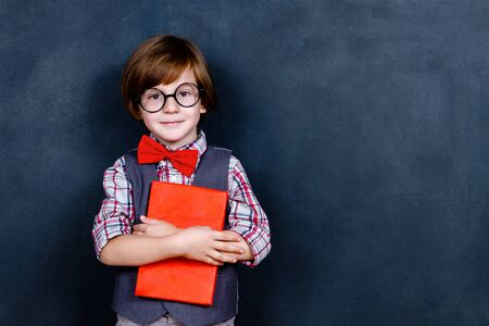 Photo pour Intelligent smart schoolboy boy with eye glasses and red tie bow holding red study book opposite school chalkboard at school. Back to school, ready to study concept - image libre de droit