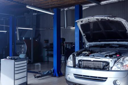 Photo for Silver car with open hood at service station garage. Modern workshop auto repair shop with hydraulic lift, special equipments and tools to repair, maintenance and conduct diagnostics of vehicles. - Royalty Free Image