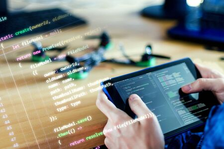 Photo for Programmer is holding tablet with program code of software for controlling FPV drone. Developer is building quadcopter from kit with microcontrollers at workplace. Desktop of hardware engineer. - Royalty Free Image