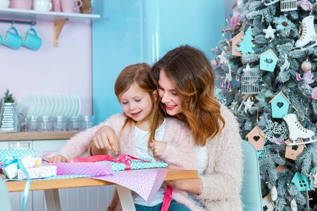 Photo for Smiling woman and little girl child are sitting at table in light christmas kitchen. Mom and daughter are packing presents with colorful paper. Family preparation for celebration happy new year. - Royalty Free Image