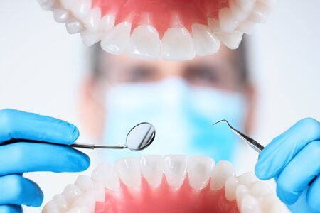 Photo pour Closeup of open human jaw with teeth. Portrait of man dentist orthodontist doctor in medical mask is examining patient with dental instruments, tools in clinic. Tooth diseases, dentistry concept. - image libre de droit
