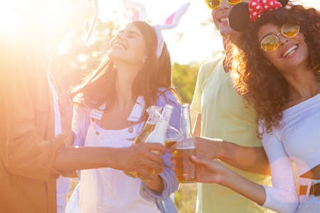 Photo for Group having fun enjoying refreshing beverage. Young men and women drink beer on festival, birthday . Happy friends spending free time together in park sitting on grass, drinking beer and chatting. - Royalty Free Image