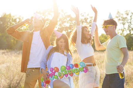 Photo for Happy excited friends having fun outdoor celebrating. Young millenial people enjoying summertime together at garden party - Cheerful friendship concept. Birthday Party festival concept. - Royalty Free Image