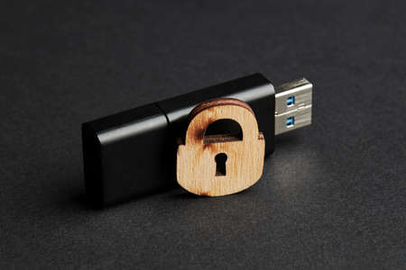 Photo pour digital security for electronic privacy data concept. dark moody photo. black usb stick with wooden lock over matte background - image libre de droit