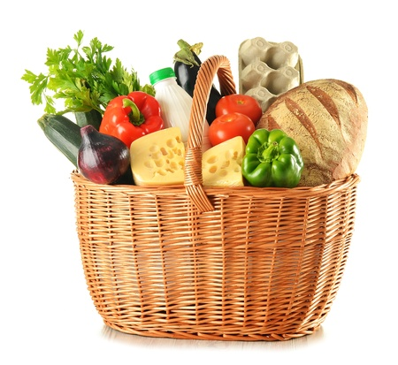 Groceries in wicker basket isolated on whiteの写真素材