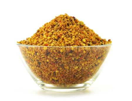Bowl with bee pollen isolated on white. Nutritional supplement