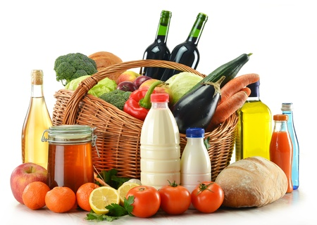 Composition with raw food including vegetables, fruits, bread and wine presented in wicker basket isolated on whiteの写真素材