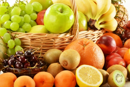 Composition with assorted fruits in wicker basket isolated on whiteの写真素材