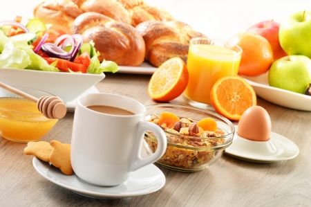 Breakfast including coffee, bread, honey, orange juice, muesli and fruitsの写真素材